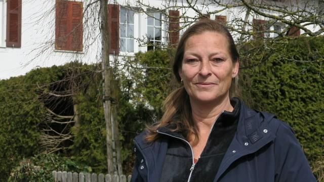 Eine Frau in blauer Jacke steht vor einer Hecke.