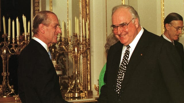 Prinz Philip schüttelt Bundeskanzler Helmut Kohl die Hand. Beide Männer in den schwarzen Anzügen lachen.