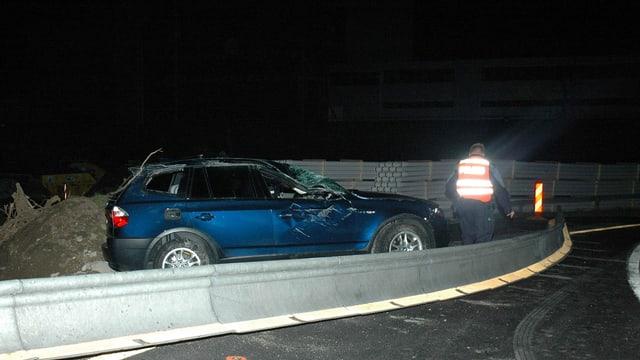 Ein zerstörter BMW-Jeep hinter einer provisorischen Leitplanke.