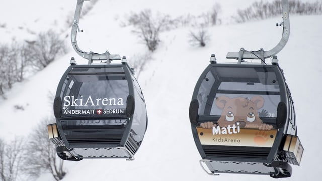 Zwei Gondeln der Ski Arena Andermatt Sedrun in der Luft.