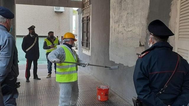 Arbeiter übermalt Wandbild