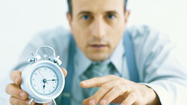 Ein Mann mit Kravatte sitzt an einem Pult und zeigt einen Wecker