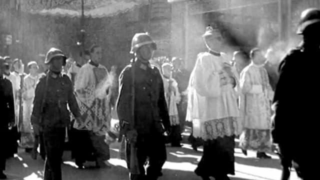 Eine Prozession mit katholischen Würdenträgern und Soldaten.