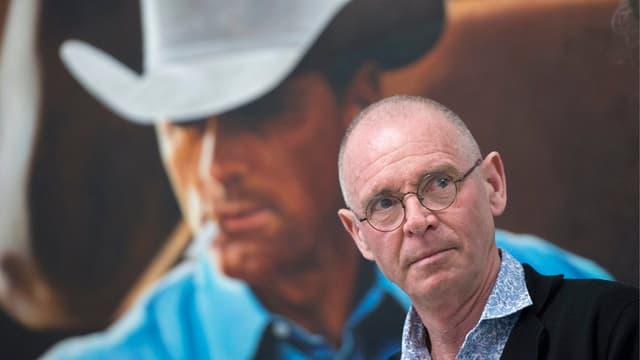 Hannes Schmid. Im Hintergrund ein Bild eine Cowboys.