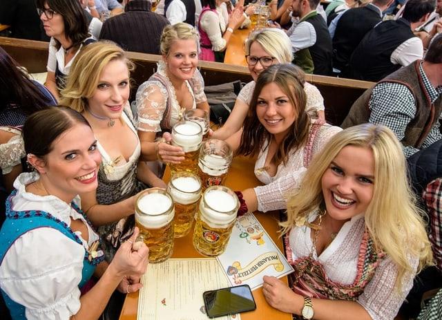 Besucherinnen prosten sich im Festzelt mit ihrer ersten Mass Bier zu.
