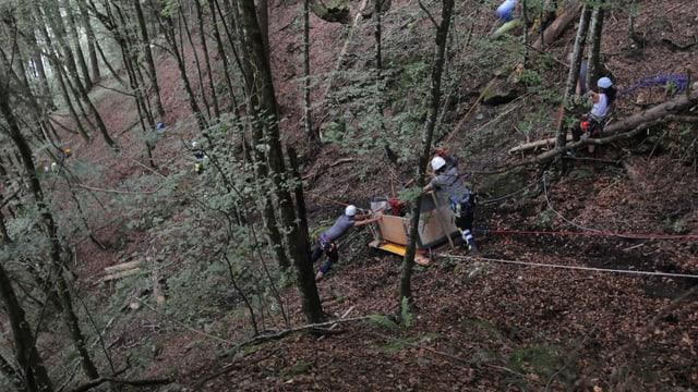 Einsatzkräfte bergen in einem Wald die in Innerthal abgestürzte Transportseilbahn.