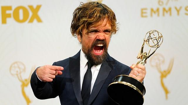 Peter Dinklage schreit und zeigt auf den Emmy.