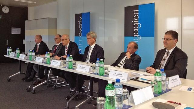 Medienkonferenz der AKB: Viele schwarz gewandete Herren an einem Tisch.