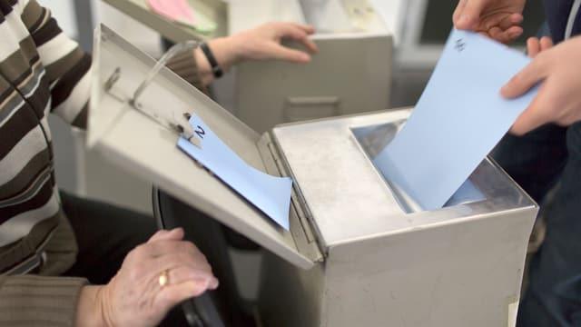 Eine Person wirft einen Stimmzettel in eine Wahlurne