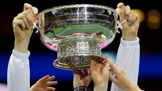 Hände am Siegerpokal des Fed Cups