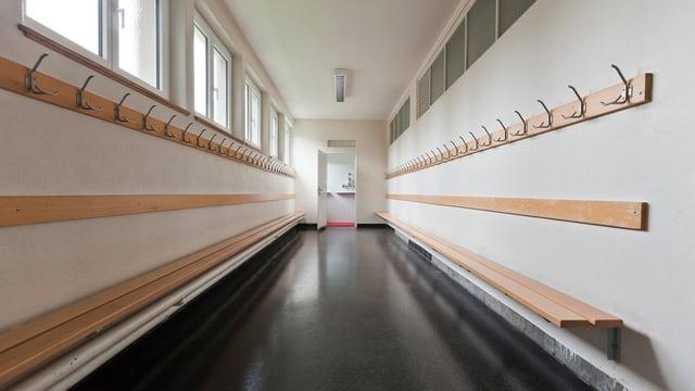 Ein leeres Schulhaus von Innen. An den Wänden auf beiden Seiten sind Bänke und Kleiderhacken angebracht.