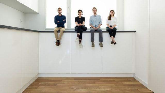 Vier Menschen sitzen in einer überdimensional grossen Küchen auf einer ABlagefläche.