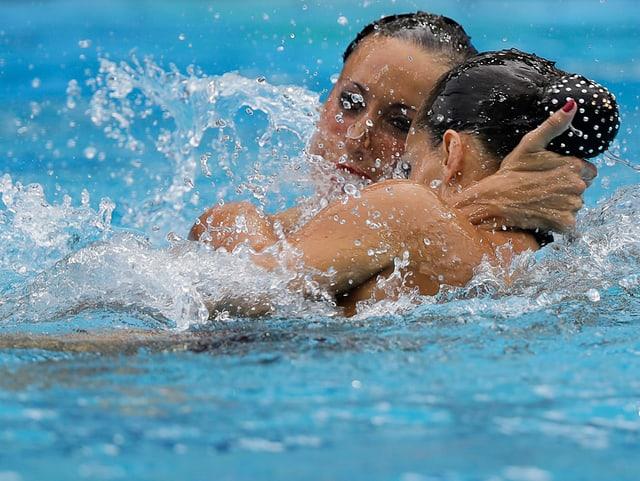 Schwimmerinnen halten sich am Kopf.