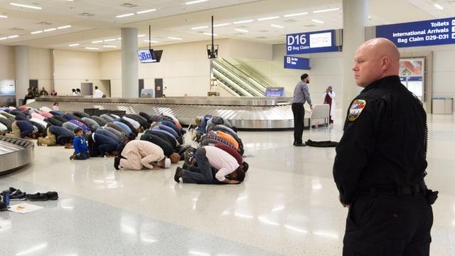 Betende Männer in einer Ankunftshalle.