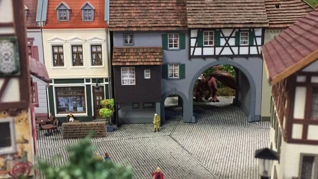 Eine Alstadt in Kleinformat. Durch einen Torbogen sieht man die Umrisse eines Drachen.