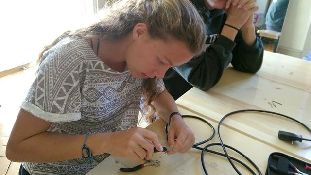 Eine junge Frau arbeitet mit einem Elektrokabel.