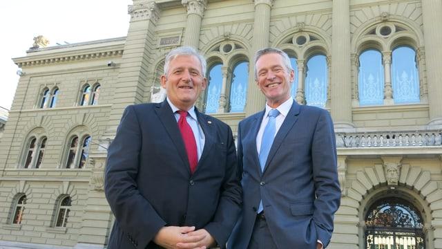 Stöckli und Luginbühl stehen vor dem Bundeshaus und lachen in die Kamera.