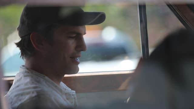 Ein Mann mit Basecap sitzt in einem Auto.