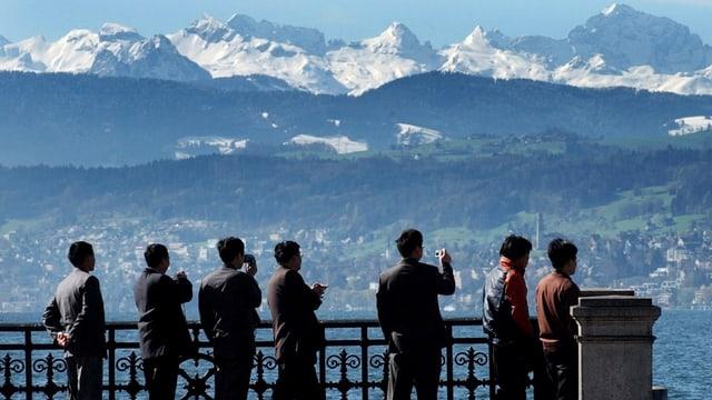 Touristen stehen auf einem Aussichtspunkt und fotografieren das Panorama
