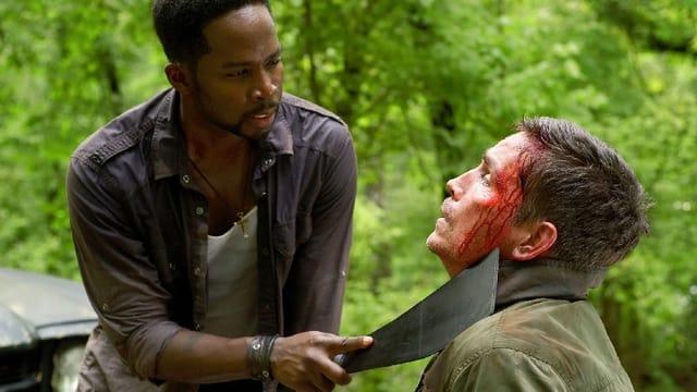 Ein Mann hält einem anderen Mann eine Machete an den Hals.