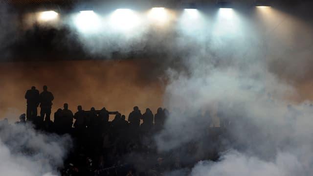 Schwarze Silhouetten von Fans in einem Stadion voller Rauchschwaden