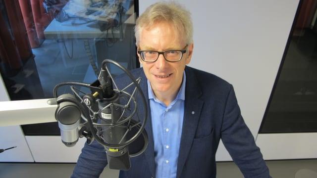 Mann mittleren Alters hinter Mikrofon in Radiostudio