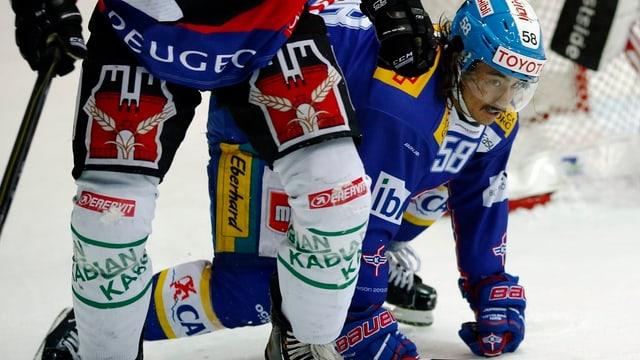 Eishockeyspieler der National League A. Ihre Hosen und Schoner zieren Bierwerbung.