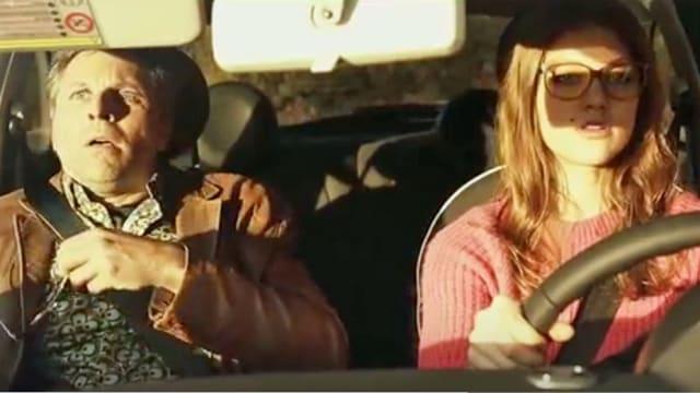 Ein Mann sitzt ängstlich neben einer jungen Fahrerin.