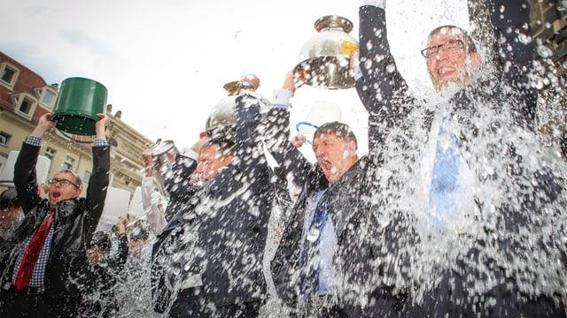 Vier Männer in Anzügen übergiessen sich mit Eiswasser aus Kübeln