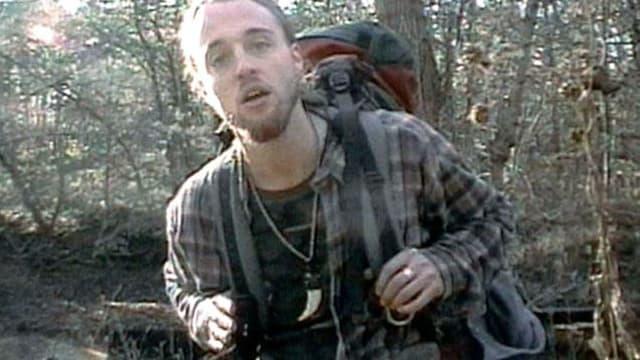 Ein junger Mann mit Rucksack steht im Wald und blickt in die Kamera.