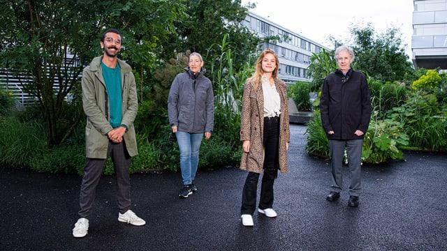 Vier Personen posieren vor einem Gebäude.