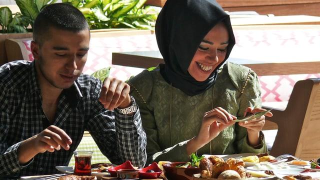 An einem Tisch sitzen essend ein junger Mann und eine lachende junge Frau.