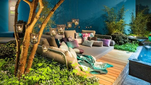 Eine Lounge mit vielen Kissen und Lampen neben einer Wasserwelt