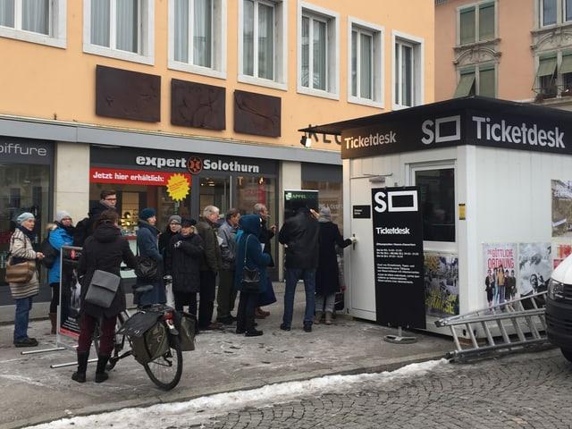 Eine Menschenschlange steht vor einer Baracke mit der Aufschrift «Ticketdesk».