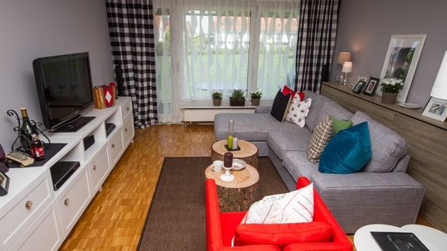 Das Bild  zeigt den gesamten Wohnbereich mit dem Sofa auf der rechten Seite und dem Sideboard mit Fernseher auf der linken Seite. Karierte Vorhänge bilden einen Akzent.