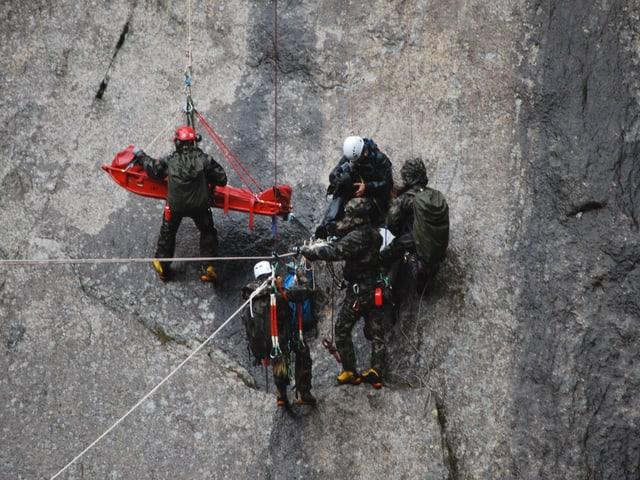 Drei Rettungshelfer, ein Kameramann und Nik Hartmann auf der Trage mitten in der fast. senkrechten Felswand.