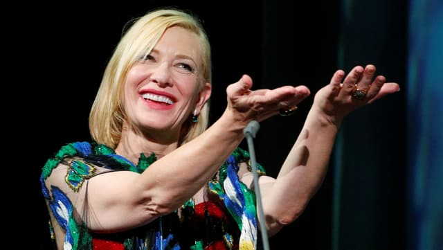 Kate Blanchett strahlt in die Kamera und streckt beide Hände nach vorne.