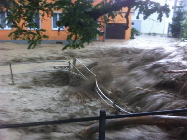 Wasser, Gehölz und Geröll schieben ein Geländer beiseite.