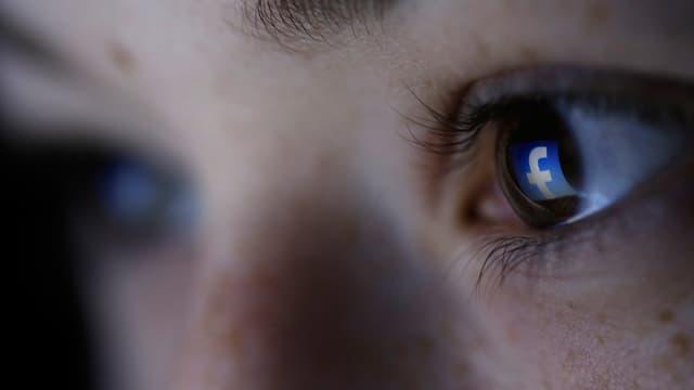 Grossaufnahme eines Auges; darin spiegelt sich das Facebook-Logo.