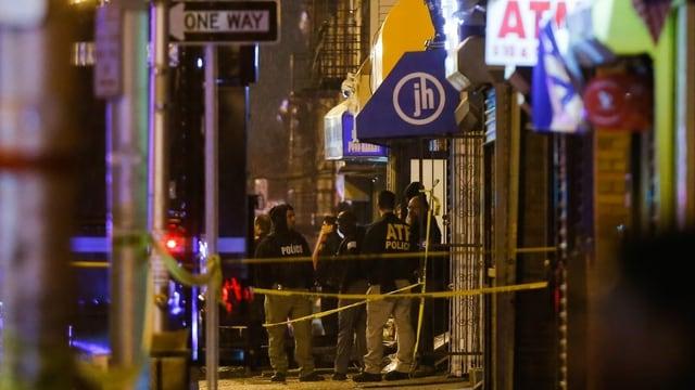 Polizisten mit Schutzwesten stehen nachts vor Geschäften in einer Strasse von Jersey City. Gelbe Bänder sichern den Tatort.