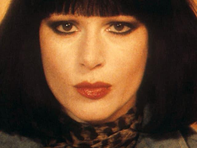 Porträt (nah) von Manon. Sie trägt einen dunklen Pagenschnitt und einen Schal mit Tigermuster.