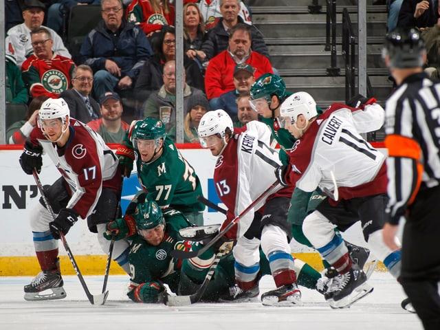 6 Eishockeyaner kämpfen auf engstem Raum gegeneinander.
