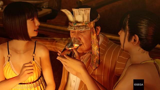 Ein Mann mit Geld am Kopf lässt sich von zwei Hostessen tränken.