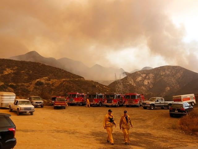 Berge mit Rauch, gelbes Licht, Feuerwehrleute