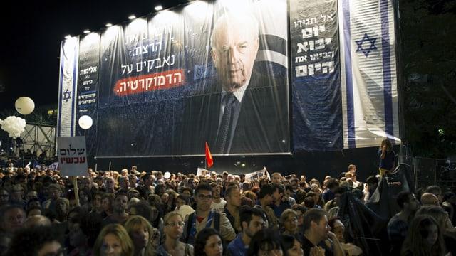 Gedenken in Tel Aviv. Viele Menschen im Vordergrund, hinten ein grosses Plakat mit dem Gesicht Rabins.