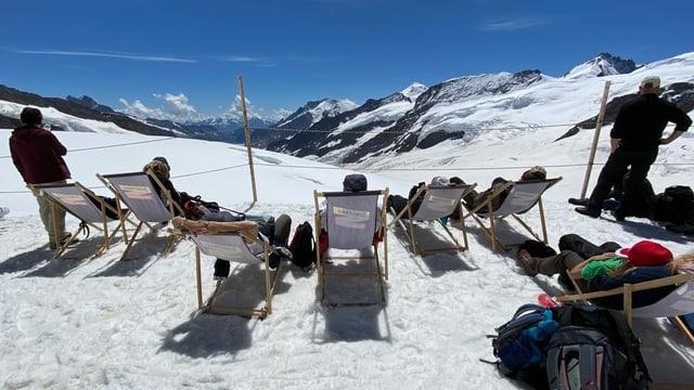Leute liegen in Liegestühlen im Schnee.