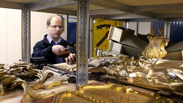 Marcus Hütten begutachtet die Kruzifixe, die sich im Zivilschutzkeller angesammelt haben.