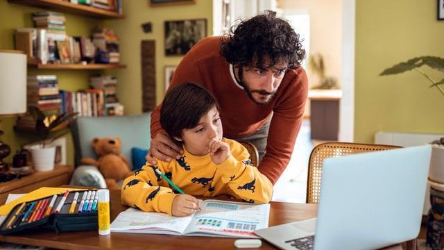Ein Vater hilft seinem Sohn bei den Hausaufgaben vor dem Laptop.