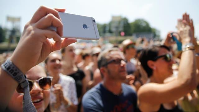 Blick ins Publikum, das mit Kameras das Geschehen festhält.