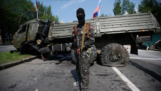 Ein vermummter pro-russischer Kämpfer steht vor einem zerstörten Armeelastwagen.